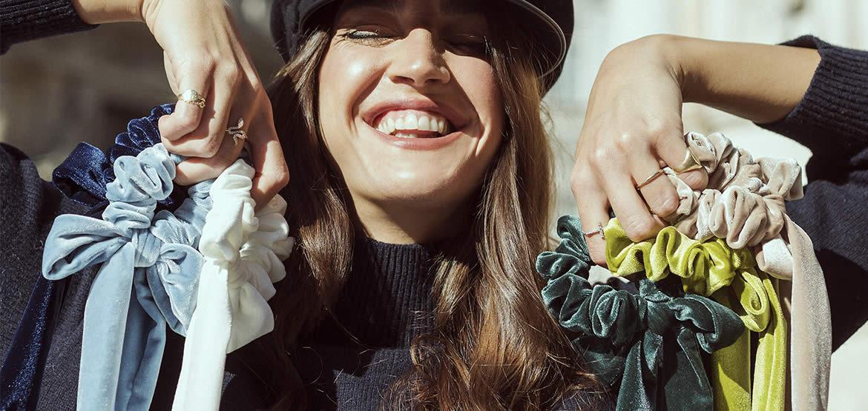 ragazza sorridente con scrunchies colorati in mano
